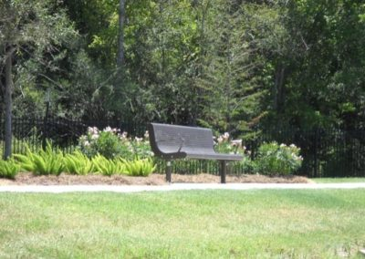 An empty bench surrounded by flowers and trees at Floral Gardens