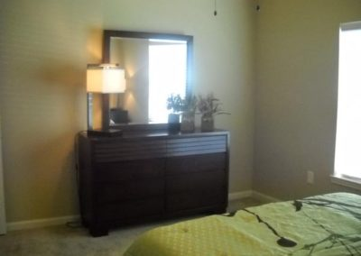Bedroom at Floral Gardens with a dark brown dresser and mirror