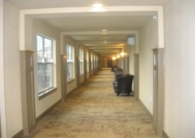 Hallway at Floral Gardens with carpet flooring and large windows