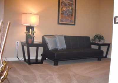 Living room with carpet flooring, black couch, and two side tables