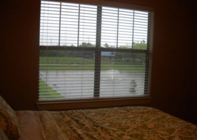 Bedroom with a large window overlooking the community pond